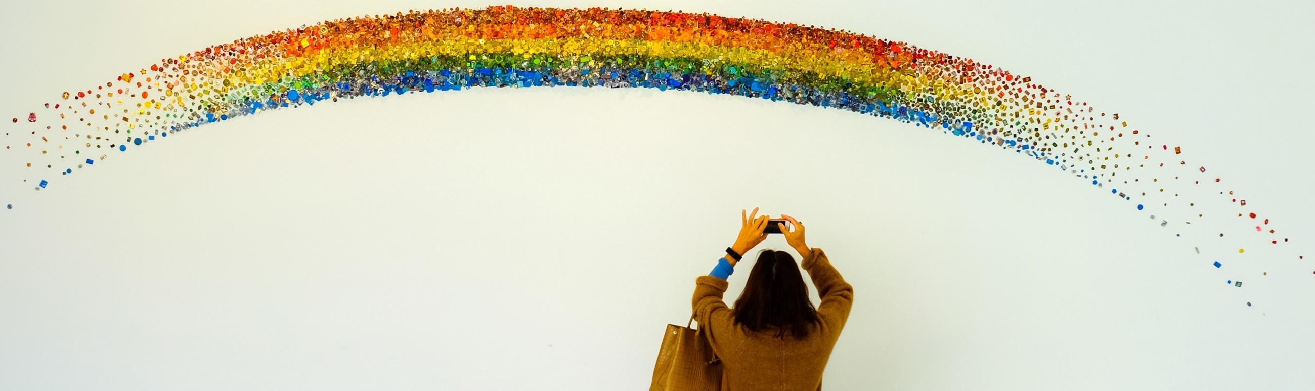 girl taking a photo of a rainbow